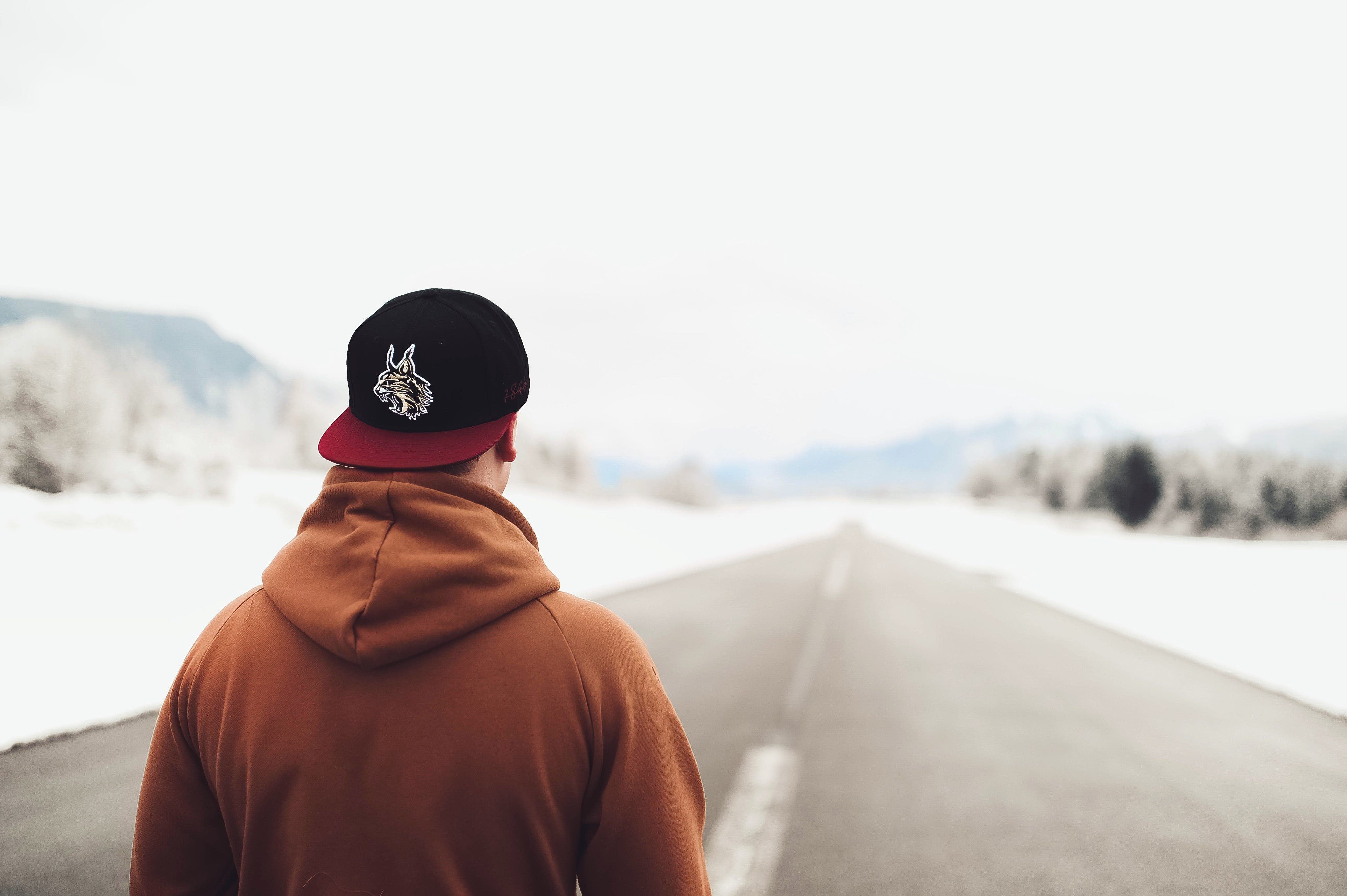 Person in Brown Hoodie and Fitted Cap Walking on Road