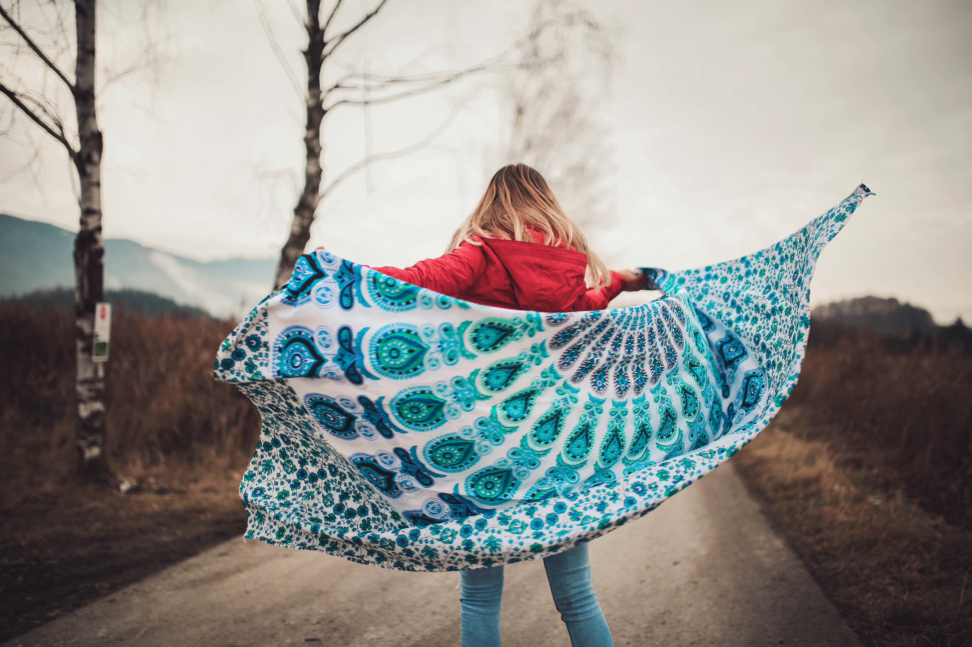 Woman Standing on the Middle of the Road Holding Blanket