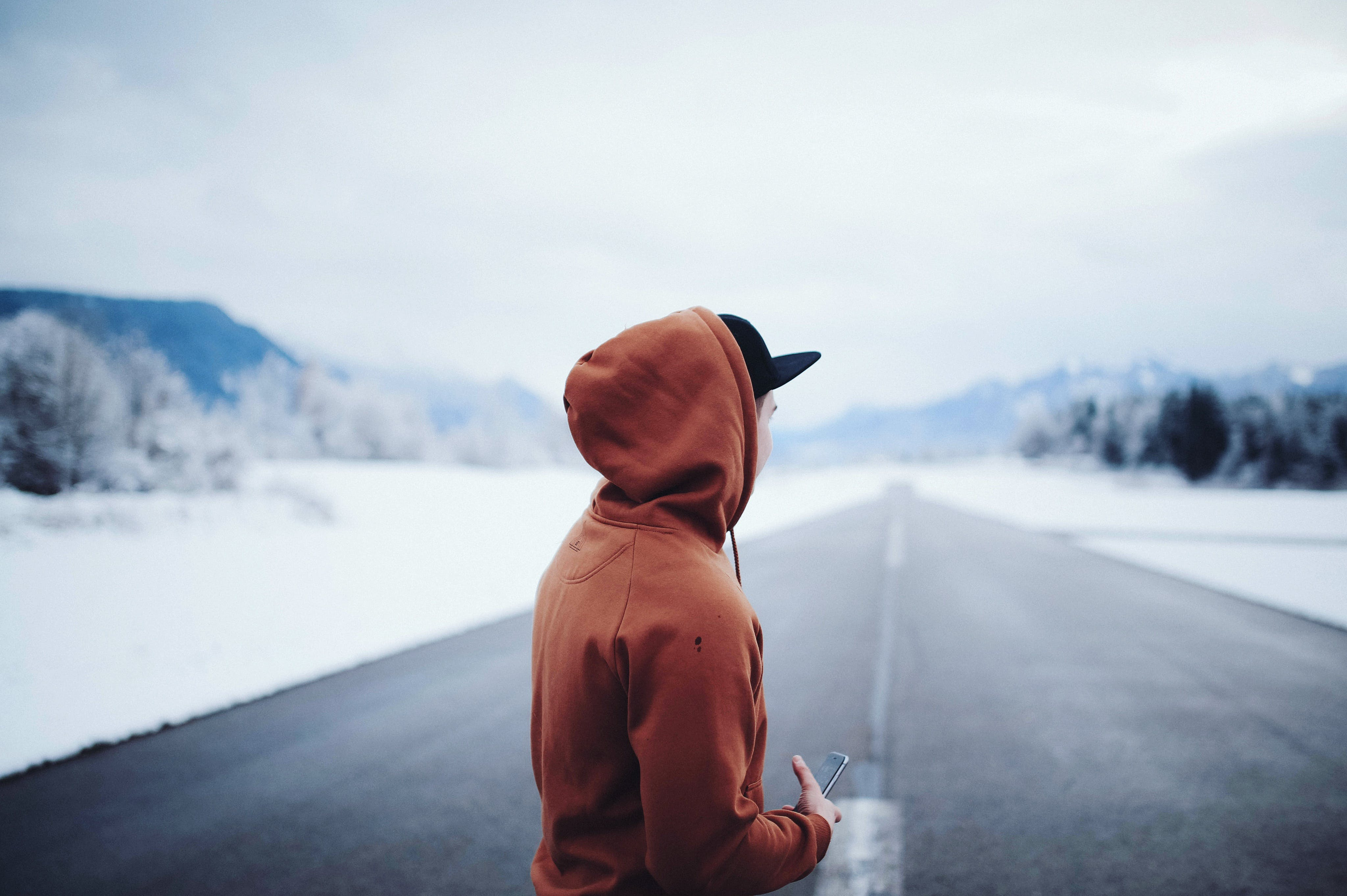 Man Wearing Brown Hoodie in Road
