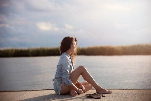 Woman In Blue Denim Jacket Sitting Near Body Of Water