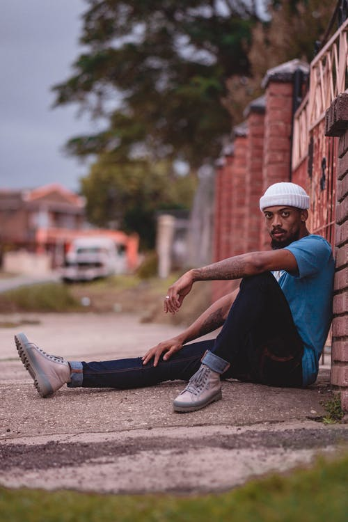 Man Wearing a Beanie Sitting on the Ground
