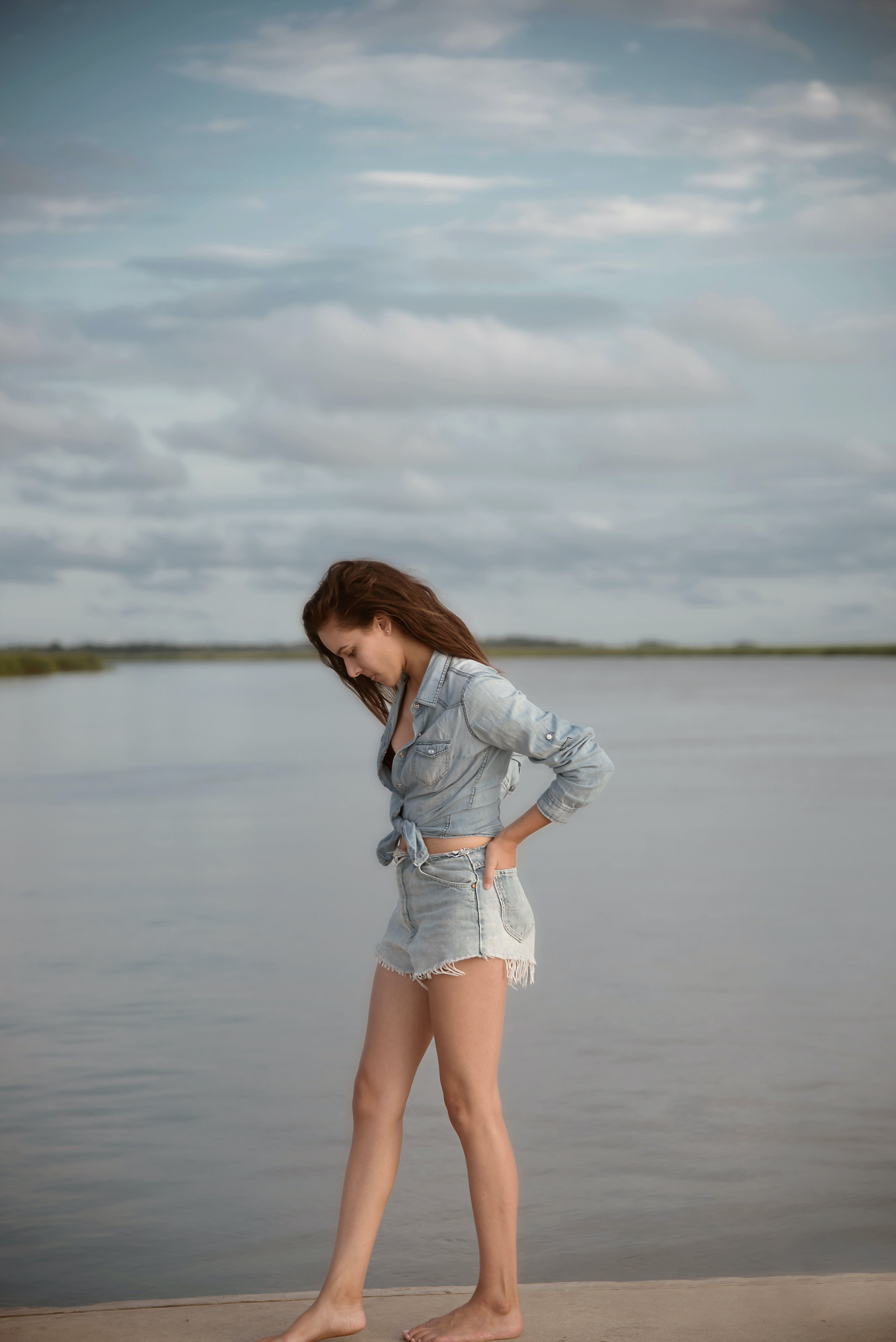 Woman Wearing Gray Denim Tie-front Long-sleeved Shirt and Short Shorts Walking on Isle Near Body of Water