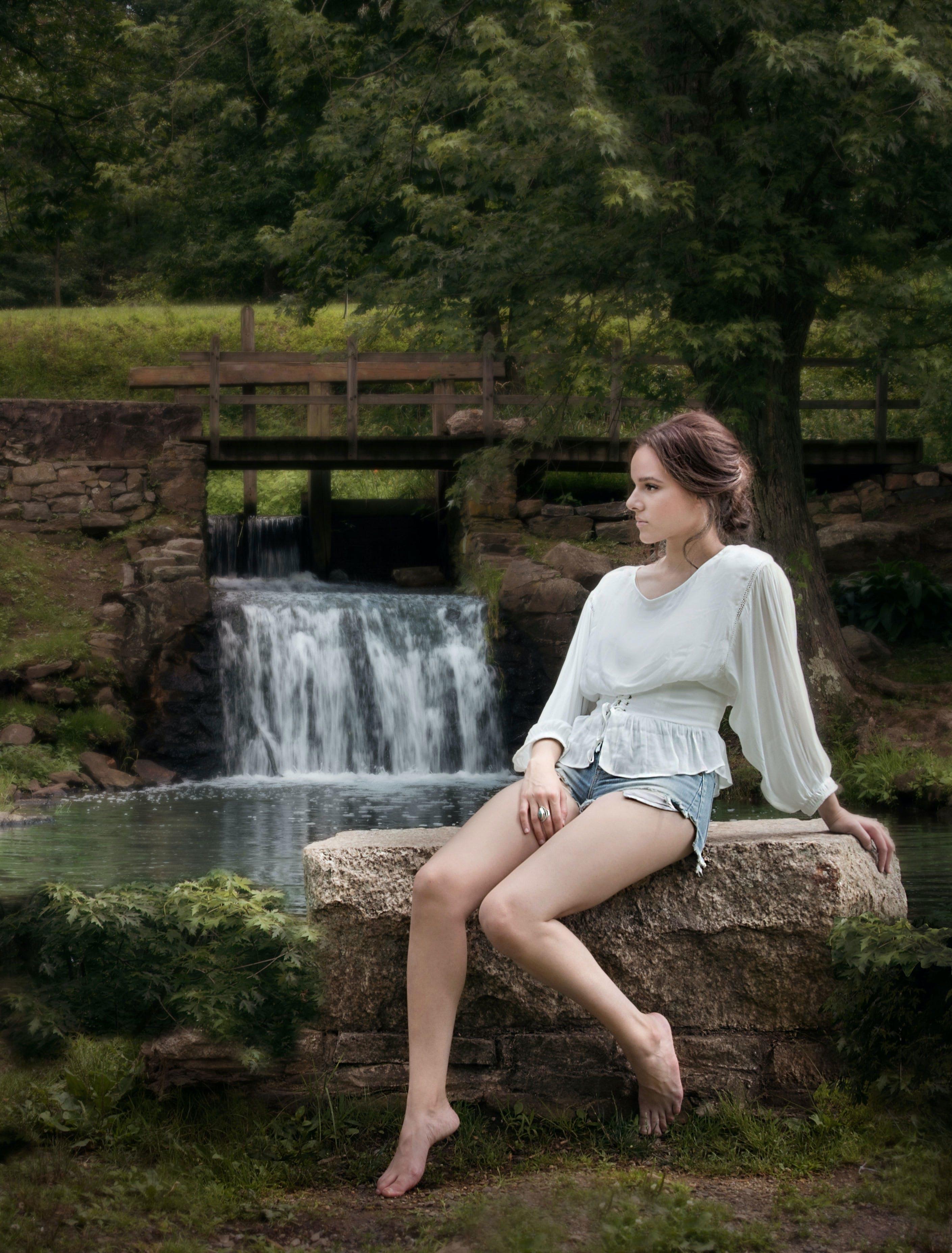 Woman Wearing White Long Sleeve Shirt Sitting Near Waterfalls
