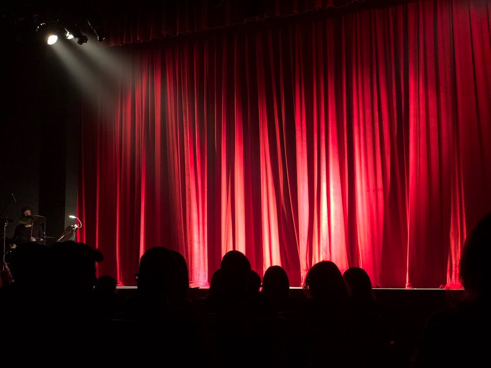 People at Theater with Red Curtain
