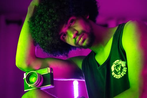 Serious black man with photo camera in neon lights