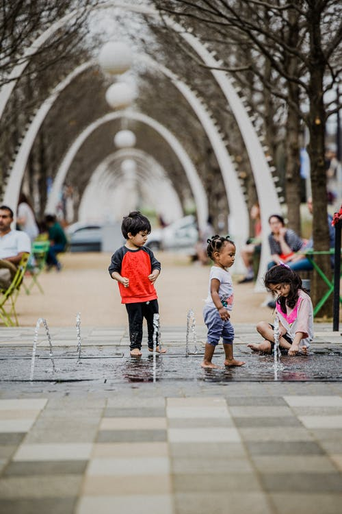 Multiethnic kids playing in fountain