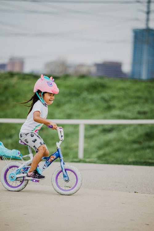 Smiling ethnic girl riding bicycle in park