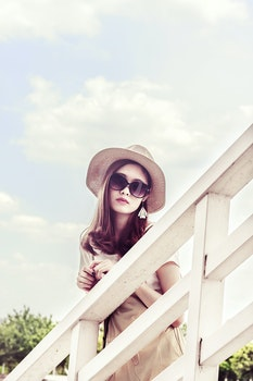 Woman Wearing Gray Sun Hat in Front of White Fence