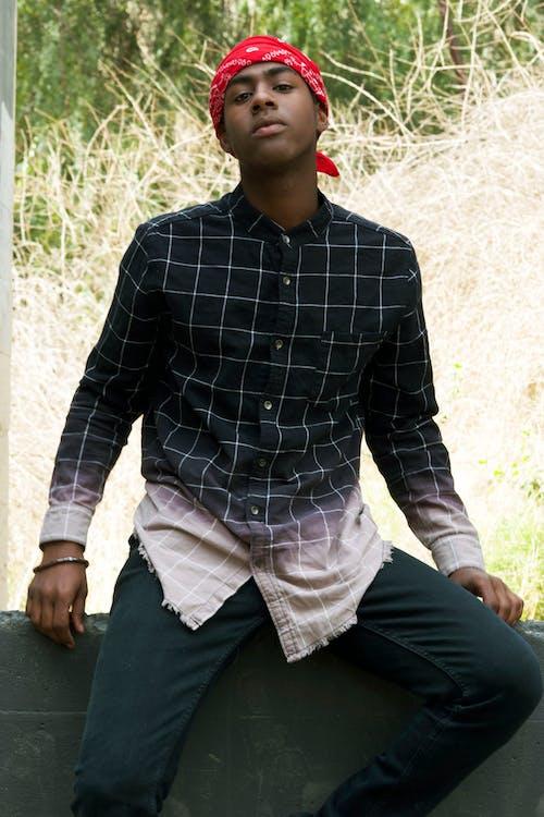 Stylish black man in checkered shirt on fence