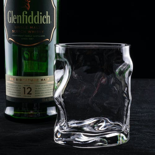 A Drinking Glass Beside a Alcohol Bottle