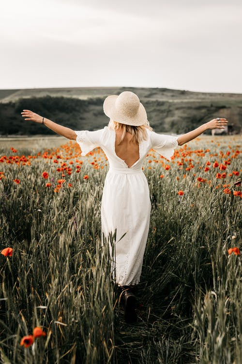 Back view full body of stylish female in white dress and headwear strolling with spread arms on grassy meadow with blooming flowers