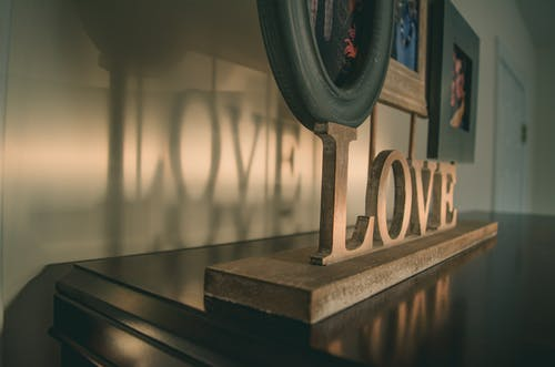 Brown Wooden Love Free Standing Letter on Black Wooden Surface