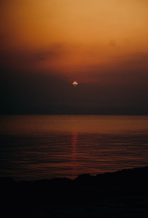 Scenery view of wavy ocean and coast under bright cloudy sky with sun at night