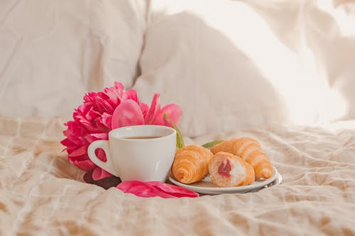 Cup of fresh aromatic coffee with plate of yummy croissants with berry jam placed on soft bed with gentle peony in sunny morning