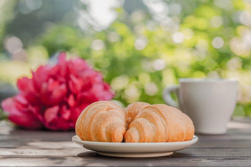 Yummy breakfast with croissants and coffee on table with fresh peony in sunlight