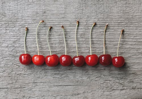 Top view of appetizing red ripe cherries placed on wooden table in row in sunlight