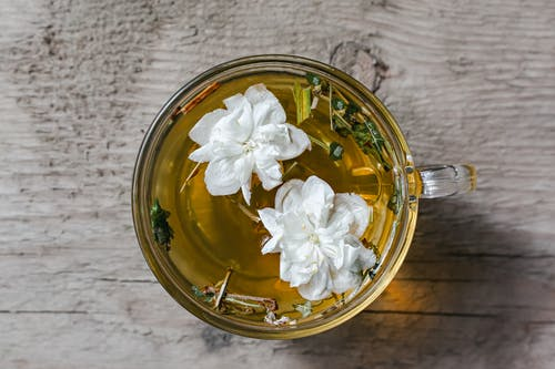 From above of aromatic herbal tea with fresh Arabian jasmine flowers in glass cup placed on wooden table in daylight