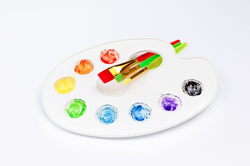 Palette with bright watercolors and brushes placed on white surface