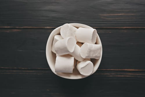 Top view of soft yummy sweet marshmallows in ceramic bowl served on wooden table