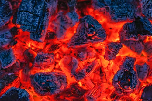 From above of many hot burning coals placed in bonfire in evening time