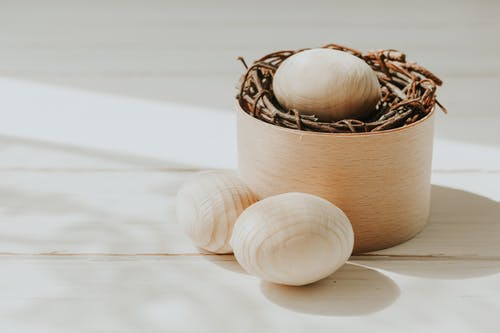 Handmade wooden eggs and decorative nest in light room