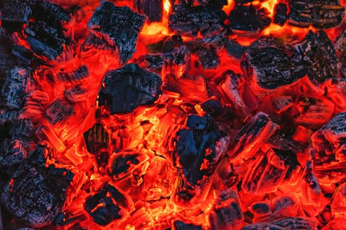 From above of bright orange hot coals placed in bonfire in evening time