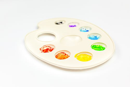 Palette with colorful paints on white background