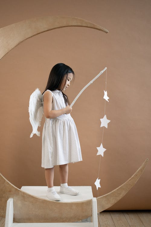 Cute Asian girl in angel costume with wand in decorative crescent moon