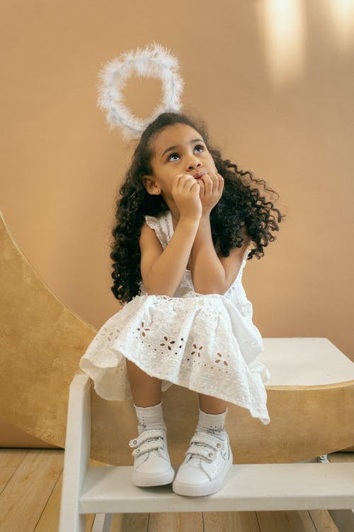 Full body of adorable African American girl in white angel costume with halo looking up while sitting on white step on brown background