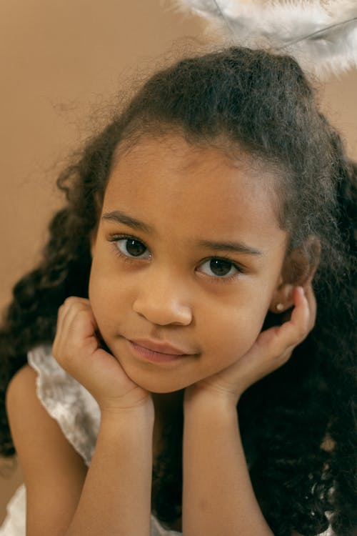 Cute African American girl with curly hair and brown eyes wearing angel nimbus leaning on hand and looking at camera