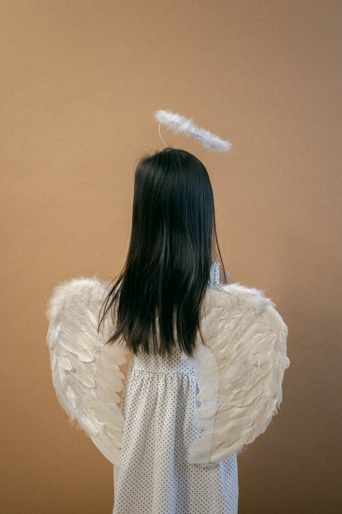 Small girl wearing angel costume standing near beige wall
