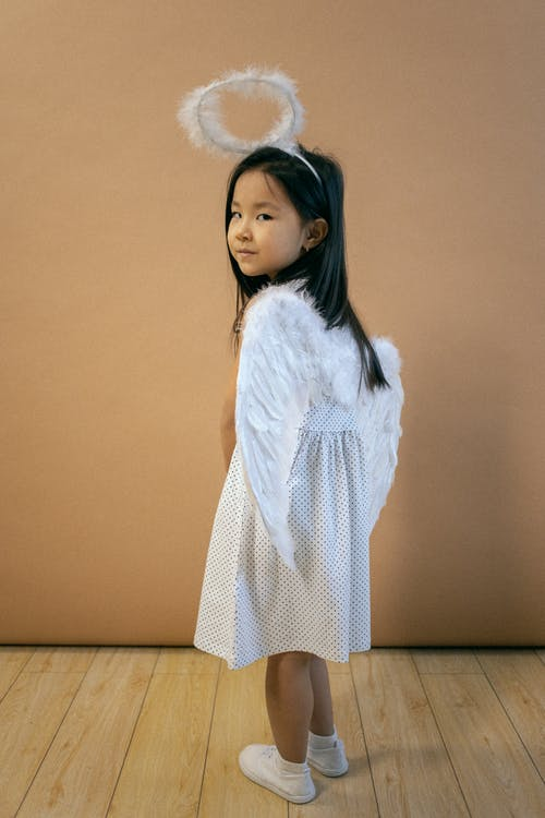 Cute Asian girl in white angel outfit