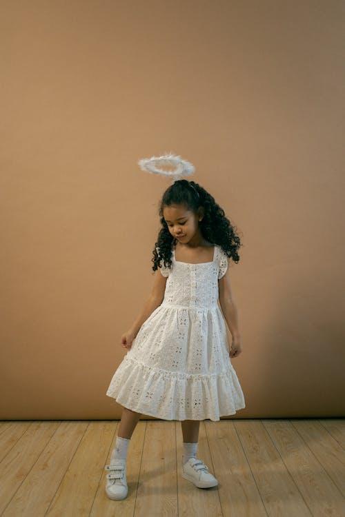 Cute black girl in angel costume in studio