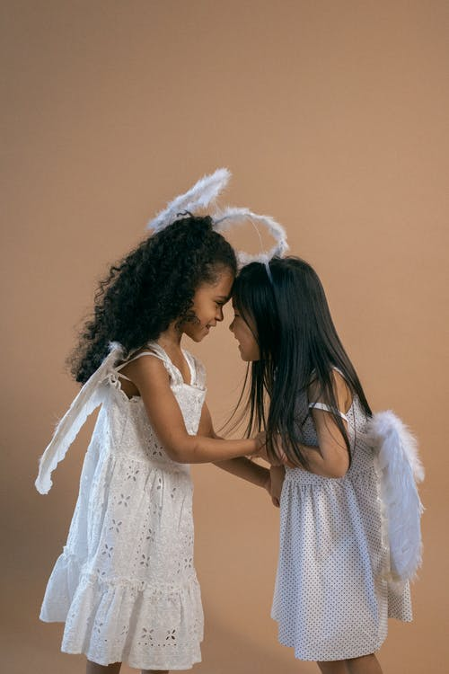 Side view of adorable smiling African American girl touching forehead of Asian best friend wearing angel outfit against brown background