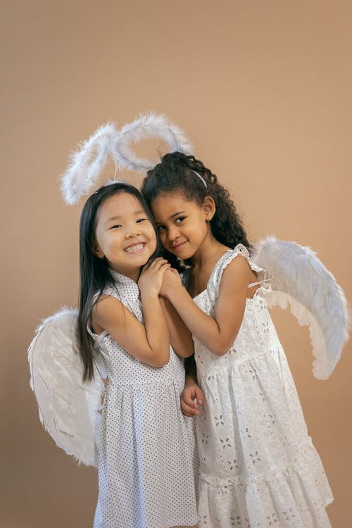 Positive multiracial girls with black hair in white angel costumes with wings and halos standing on brown background in light studio