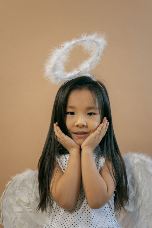 Content Asian girl in white wings and nimbus looking at camera while leaning on hands on brown background in studio