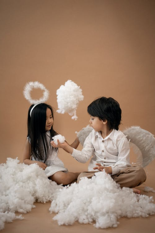 Diverse children in angel costumes playing with cotton