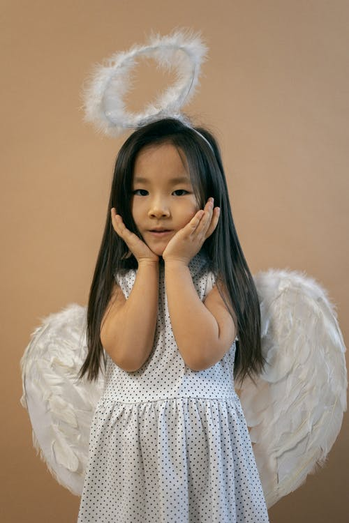 Adorable Asian girl in white angel costume with wings and nimbus looking at camera while leaning on hands on brown background