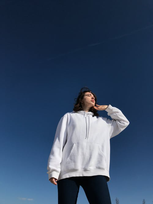 Low angle of peaceful female with closed eyes in casual hoodie and jeans standing against blue sky