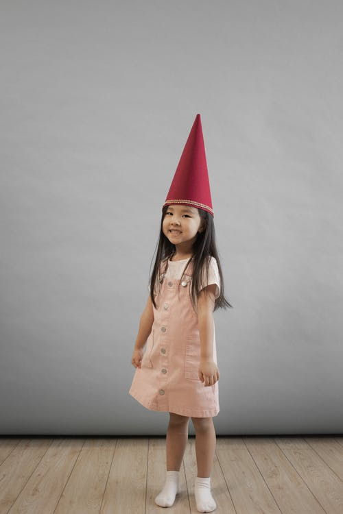 Full body of cheerful Asian girl in red gnome hat looking at camera while standing on gray background in studio