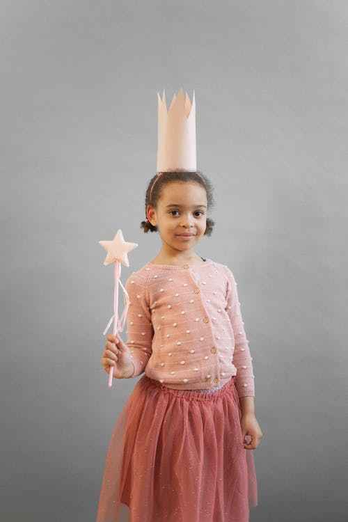 Cheerful African American girl wearing princess crown looking at camera while standing on gray background with magic wand in hand