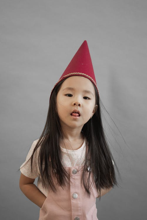 Adorable Asian girl with black hair wearing red gnome cap looking at camera while standing on gray background in studio