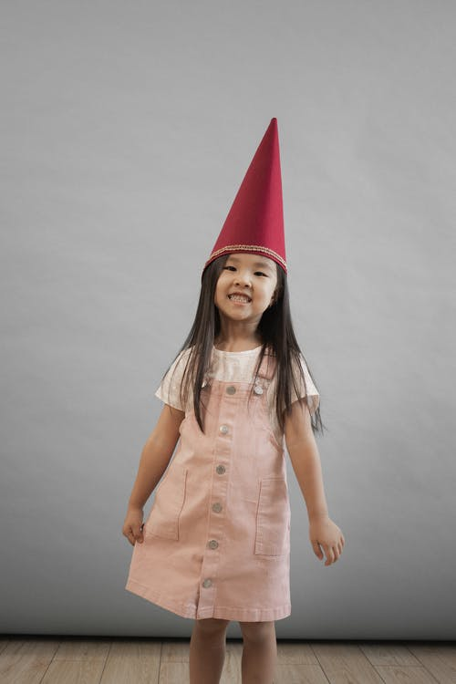 Delighted Asian girl in red gnome cap smiling and looking at camera while standing on gray background in light studio