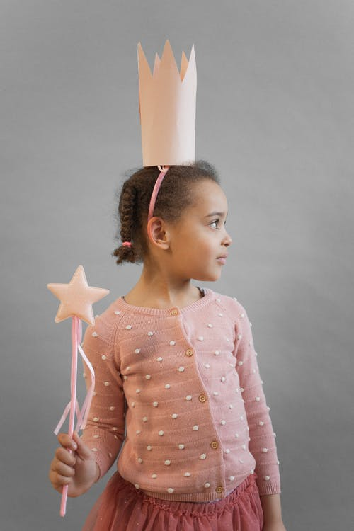 Cute African American girl wearing princess costume with crown and magic wand while standing on gray background in light studio
