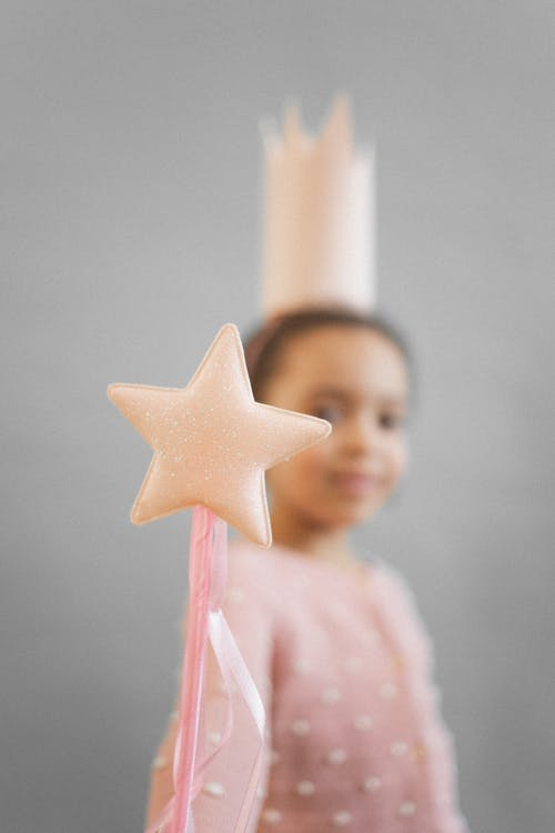 Soft focus of anonymous African American girl in princess crown showing magic wand while standing on gray background in studio