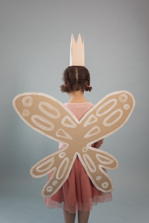 Back view of unrecognizable girl with black hair wearing crown and wings standing on gray background in modern light studio