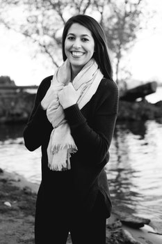 Grayscale Photography of a Woman Wearing Sweatshirt and Black Pants While Holding Scarf