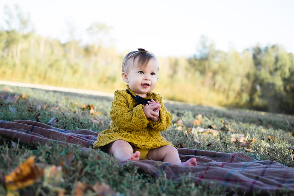 Image of a happy toddler sitting on a blanket in a field.