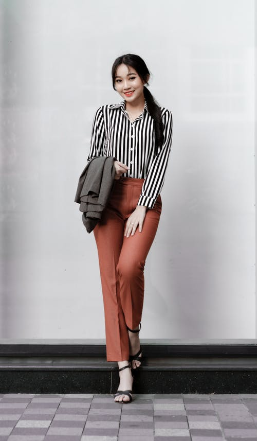 Woman in Black and White Striped Long Sleeve Shirt and Orange Pants