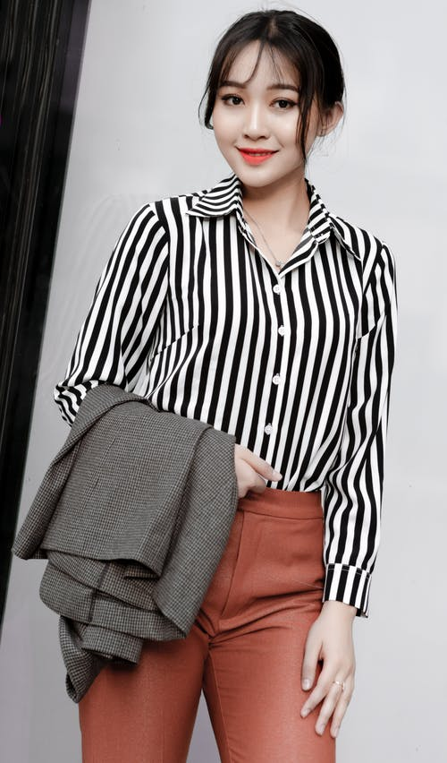 Woman in Black and White Striped Button Up Shirt and Orange Skirt